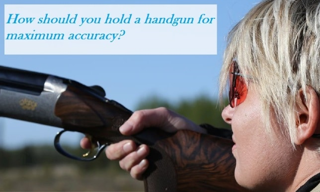 How should you hold a handgun for maximum accuracy?